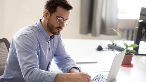A man doing a search on his computer for an internet marketing company